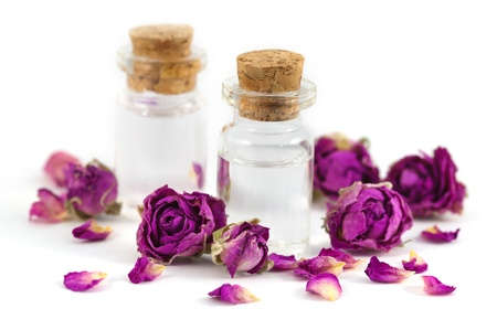 aromatherapy oils: Two fragrance s bottles filled with rose aroma oil with purple dried rose buds and petals isolated on white background