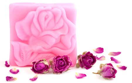 glycerin soap: Pink bar of natural rose soap with dried purple rose buds on white background  Stock Photo
