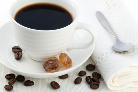 Small white porcelain cup of hot black turkish coffee, caramel brown sugar crystals, small stainless steel spoon and coffea arabica beans served on white table-cloth photo