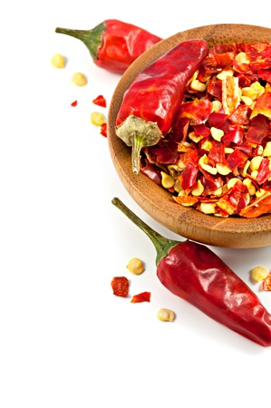 Wooden bowl with dried crushed chili red pepper isolated Standard-Bild