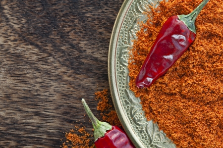Oriental copper plate with dried crushed chili red pepper powder and whole dried chili peppers on dark wood background  Oriental spicy food concept  photo