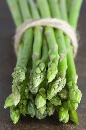 Close up picture of ripe fresh green asparagus on a wooden table  photo
