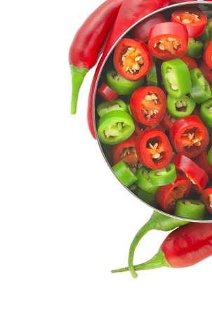 Modern steel bowl with fresh ripe whole and sliced red and green chili red pepper with selective focus isolated on white background  Spicy cuisine concept