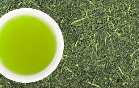 sencha: Cup of green tea and green tea leaves background Stock Photo