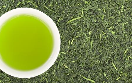 Kopje groene thee en groene thee bladeren achtergrond