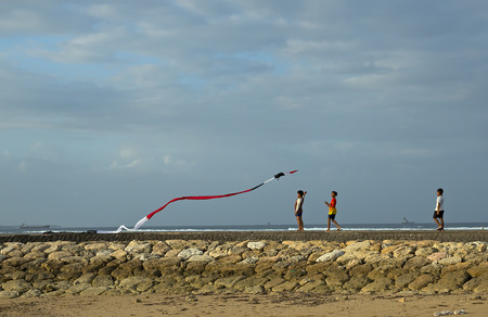 rural community: Bali, Indonesia - August 14, 2014: People try to fly a kite on a windy day at the Nusa Dua Beach. Kite flying and kite fighting are most popular recreation activity for the Balinese rural community.