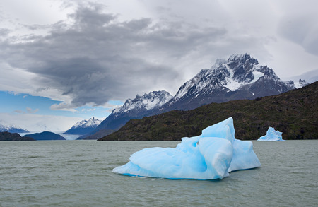 Shatter of blue iceberg in front of The Gray Glacier, Patagonia, Chile photo