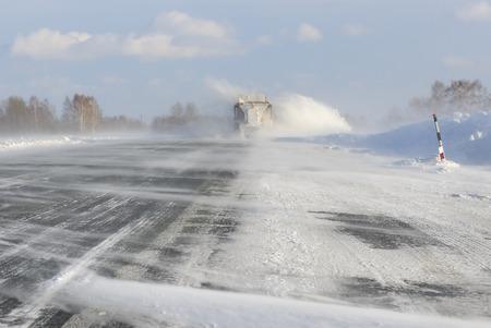 La pista di servizio stradale di emergenza pulisce la strada dopo una brillante nevicata invernale con la neve in autostrada Archivio Fotografico - 71388832