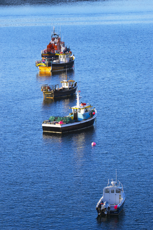Portree, United Kingdom - August 20, 2016: Fishing vessels anchored in a calm harbor of Portree, Isle of Skye, Scotland, UK. Vessels await fishing season with empty traps on deck. Stock Photo