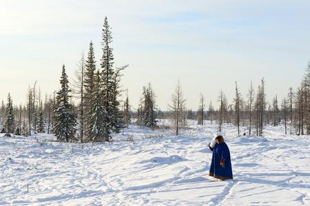 La donna della tribù indigena del Cerchio Polare porta pezzo di neve per sciogliere per la preparazione del tè. Archivio Fotografico - 73249533
