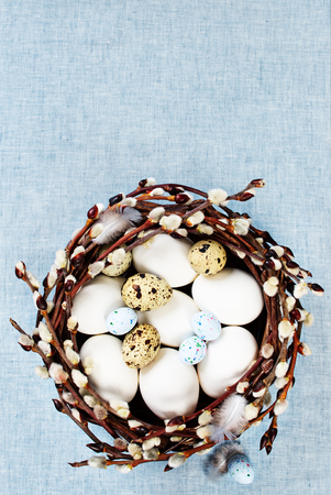 Easter decoration with blooming willow branches and colorful eggs in a basket on a blue fabric background Stock Photo