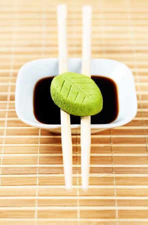 Set di isabi e fonte di soia su una tovaglia di bambù con bacchette di legno. Preparazione del pranzo. Archivio Fotografico - 76485834