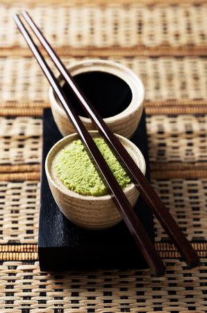 Pranzo saporito e piccante. Set di isabi e fonte di soia su una tovaglia di bambù con bacchette di legno. Archivio Fotografico - 76526807