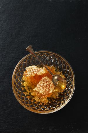 Miele, cucchiaio e nido d'ape su uno sfondo di tavola di pietra nera Archivio Fotografico - 77117103