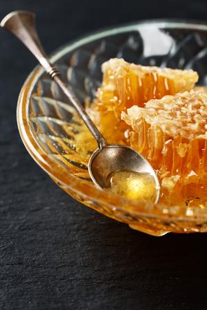 Miele, cucchiaio e nido d'ape su uno sfondo di tavola di pietra nera Archivio Fotografico - 77131570