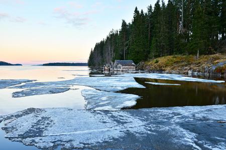 Skerry shore del lago di Ladoga con vecchie boathouse di legno al tramonto. I resti di ghiaccio coprono acqua. Archivio Fotografico - 78105736