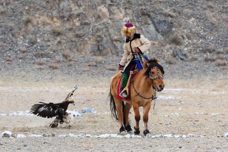 Bayan-Olgii, Mongolia - 30 settembre 2017: Il cacciatore sconosciuto con Eagle dorato mostra la sua esperienza in caccia col falcone. Archivio Fotografico - 90003851