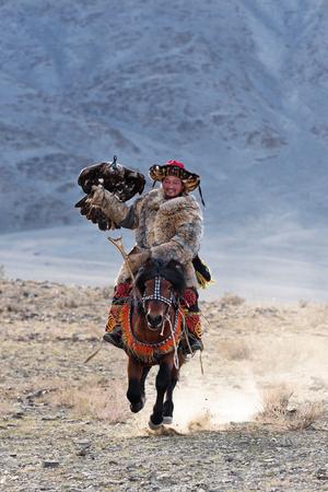 Bayan-Olgii, Mongolia - 30 settembre 2017: Il cacciatore sconosciuto con Eagle dorato mostra la sua esperienza in caccia col falcone. Archivio Fotografico - 90204197