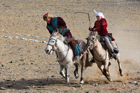 Bayan-Olgii, Mongolia - September 30, 2017: Horse riding competition during Golden Eagle festival. Local family wears traditional costumes during competition.