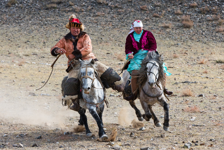 Bayan-Olgii, Mongolia - September 30, 2017: Horse riding competition during Golden Eagle festival. Local family wears traditional costumes during a competition.