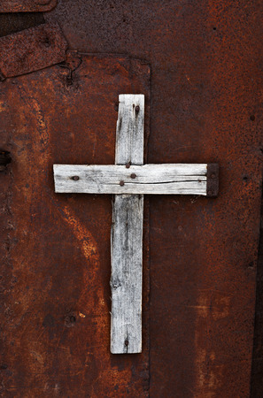 Wooden cross on a rusty door of an abandoned house Standard-Bild