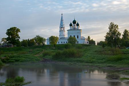 Sunrise in the tiny village Osenevo. Kazanska church reflected in a water of the river Lakhost.