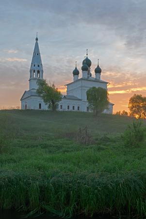 Sunrise in the tiny village Osenevo. Kazanska church under red sun rays. Standard-Bild