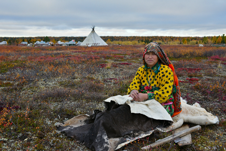 Nomad camp, Yamal peninsula, Russia-September 22, 2018: During the reindeer migration. She wears local national dress.