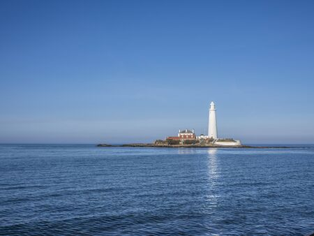 The Lighthouse on St Mary's Island Whitley Bay. The stark white of the lighthouse contrasts with the rich blue sky and the calm North Sea. Stock Photo