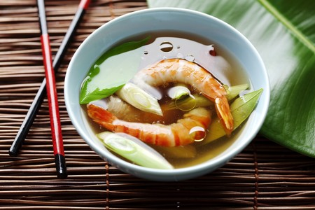 exotic food: light asian shrimp soup with kafir leaves and spring onions