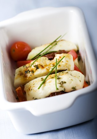 haloumi: Goatsheeps cheese from cyprus grilledbaked in the oven with red pepper,thyme,sundried tomatoes and cherry tomatoes sprinled with a little bit of paprika a chives as garnish Stock Photo