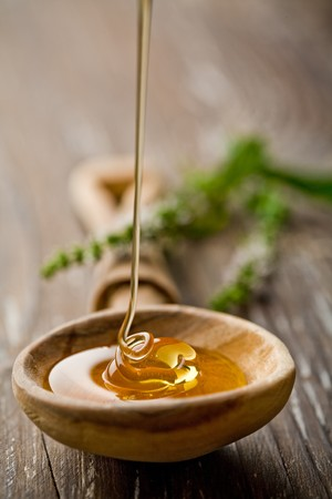 honey liquid: wooden spoon with wild honey falling into it