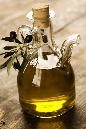 aceite de oliva: botella de aceite de oliva en la vieja mesa de madera y una rama de olivo  Foto de archivo