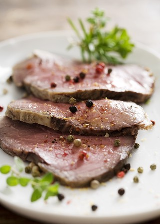 slices of juicy roast beef with herbs and pepper