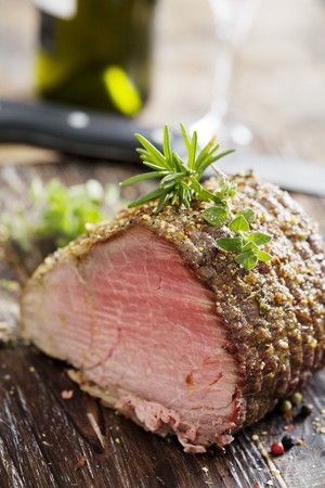 beef tenderloin: nice piece of roasted siroin beef covered in herbs