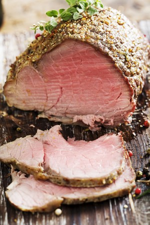 a rare: sliced rare beef, roast covered in pepper and herbs Stock Photo
