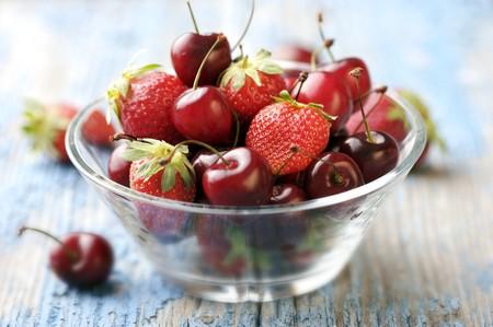 cereza: Bol de cristal de la modersn sobre una mesa rústica llenos de frutos rojos estacionales  Foto de archivo