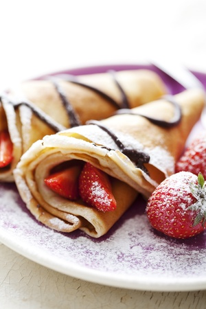 crepe: sweet thin french style crepes, served with strawberries,chocolate sauce and castor sugar, very close up and very shallow dof for a dreamy effect, focus on the strawberry in front Stock Photo