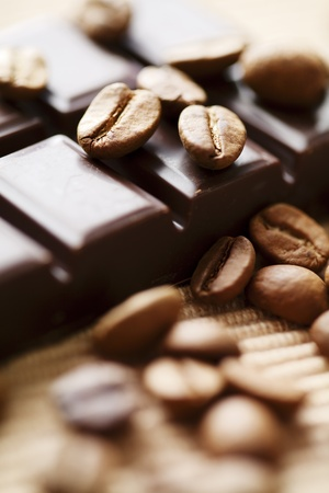 close up of dark chocolate with coffee beans around, shallow dof Фото со стока