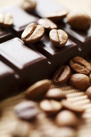 dark chocolate: close up of dark chocolate with coffee beans around, shallow dof Stock Photo