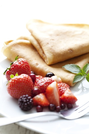 sweet thin french style crepes, served with strawberries and castor sugar, very close up and very shallow dof for a dreamy effect, focus on the strawberry in front