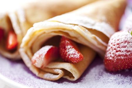 crepas: dulce fino crepas de estilo franc�s, con fresas y az�car lustre, muy cerca hasta y muy superficial dof para un efecto de ensue�o, centrarse en la fresa al frente