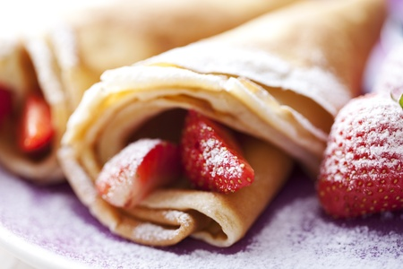 sweet thin french style crepes, served with strawberries and castor sugar, very close up and very shallow dof for a dreamy effect, focus on the strawberry in front Stock Photo - 8955504