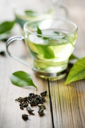 hojas de te: detalle de t� seco verde y una Copa con fresco de t� verde. en el fondo, Copa de enfoque con t� fresco