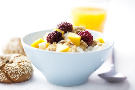 yogurt with cereal, mango and raspberry, orange juice and whole grain bagels photo