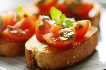close up food: sappige tomaten op vers brood, pesto als topping Stockfoto