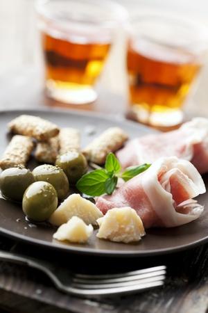 gressins: plaque avec les olives, parmesan, gressins, du fromage et proscuio, vin de pays dans l'arri�re-plan