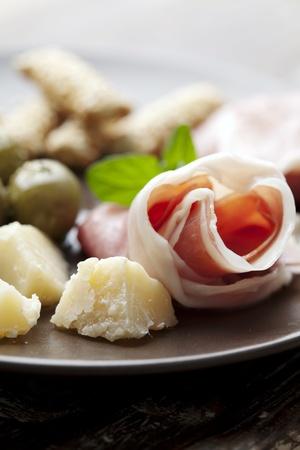 breadsticks: plato con aceitunas, queso parmesano, palitos de pan, queso y proscuio, vino del pa�s en el fondo