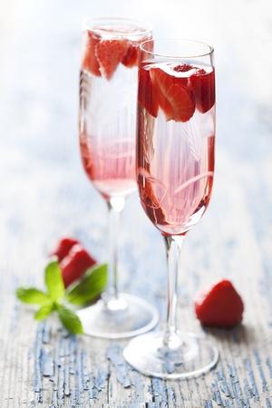 coupe de champagne: � rafra�chissant cocktail champagne fraise sur une table de jardinage rustique Banque d'images