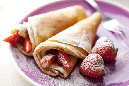 french style crepes with fresh strawberries and caster sugar Standard-Bild